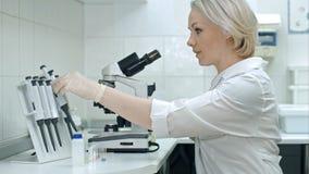 Mujer joven que trabaja con los líquidos y el microscopio Fotos de archivo