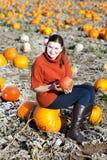 Mujer joven que trabaja en campo de la calabaza Imagen de archivo libre de regalías