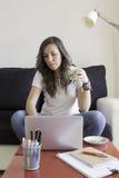 Mujer joven que trabaja en casa imagenes de archivo