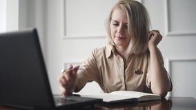 Mujer joven que trabaja en el café moderno que es oficina para los freelancers Trabajo duro de moda de la hembra adulta con los d metrajes