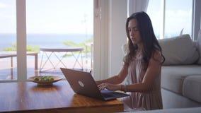 Mujer joven que trabaja en el ordenador con el coj?n del dibujo en chalet encendido almacen de metraje de vídeo