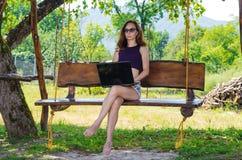 Mujer joven que trabaja en el ordenador portátil al aire libre, espacios libres Foto de archivo