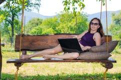 Mujer joven que trabaja en el ordenador portátil al aire libre, espacios libres Imagen de archivo libre de regalías