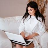 Mujer joven que trabaja en el ordenador portátil en butaca fotos de archivo