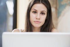 Mujer joven que trabaja en el ordenador portátil en la oficina Imágenes de archivo libres de regalías