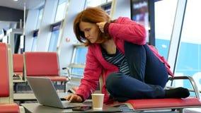 Mujer joven que trabaja en el ordenador portátil en el salón del aiport metrajes