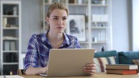 Mujer joven que trabaja en el ordenador portátil, Sittting en el sofá interno almacen de metraje de vídeo