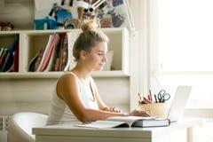 Mujer joven que trabaja en hogar-oficina acogedora Fotos de archivo