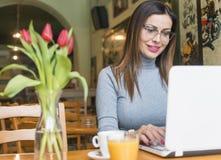 Mujer joven que trabaja en línea imagenes de archivo