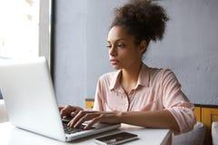 Mujer joven que trabaja en la computadora portátil Imágenes de archivo libres de regalías