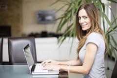 Mujer joven que trabaja en la computadora portátil Imagen de archivo libre de regalías