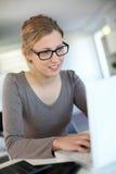 Mujer joven que trabaja en la computadora portátil Foto de archivo libre de regalías