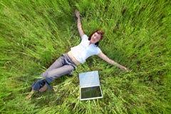 Mujer joven que trabaja en la computadora portátil en el campo Imagenes de archivo
