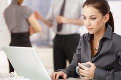 Mujer joven que trabaja en la computadora portátil en oficina Imagen de archivo libre de regalías