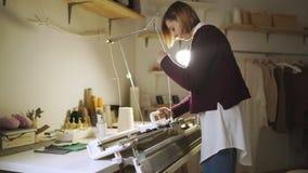 Mujer joven que trabaja en la máquina para hacer punto en el taller casero metrajes