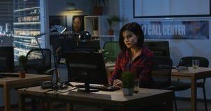 Mujer joven que trabaja en la noche en una oficina