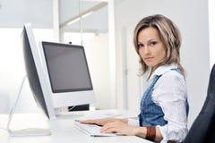 Mujer joven que trabaja en la oficina Imagen de archivo libre de regalías