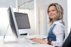 Mujer joven que trabaja en la oficina Fotos de archivo