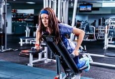 Mujer joven que trabaja en su bíceps mientras que miente en appara de entrenamiento Foto de archivo