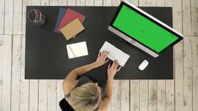 Mujer joven que trabaja en su escritorio de oficina con el ordenador Exhibición verde de la maqueta de la pantalla metrajes