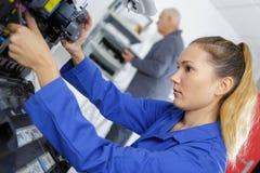 Mujer joven que trabaja en tienda del mecánico imagen de archivo