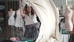 Mujer joven que trabaja en un estudio de costura la ropa de diseñador de la muchacha desecha el paño en la tabla la modista traba almacen de metraje de vídeo