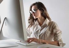 Mujer joven que trabaja en un ordenador imagenes de archivo