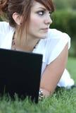 mujer joven que trabaja en una computadora portátil Imagen de archivo libre de regalías