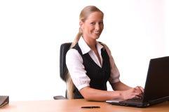 Mujer joven que trabaja en una computadora portátil y una sonrisa Fotografía de archivo