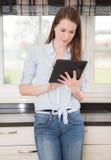 Mujer joven que usa el dispositivo de la tableta Imagenes de archivo