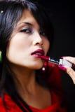 Mujer joven que usa el lisptick Fotografía de archivo
