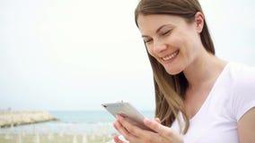 Mujer joven que usa el móvil en la playa solamente Charla femenina con los amigos vía el teléfono móvil en la cámara lenta almacen de video