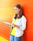 Mujer joven que usa el ordenador de la PC de la tableta en perfil sobre naranja Imagenes de archivo