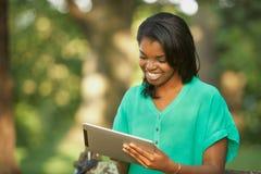 Mujer joven que usa el ordenador de la tablilla Imagenes de archivo