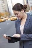 Mujer joven que usa el ordenador de la tablilla en New York City Fotos de archivo