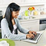 Mujer joven que usa el ordenador en cocina Fotos de archivo