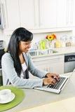 Mujer joven que usa el ordenador en cocina Fotografía de archivo libre de regalías