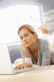 Mujer joven que usa el ordenador portátil Fotos de archivo