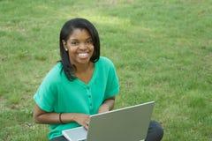 mujer joven que usa el ordenador portátil Fotografía de archivo