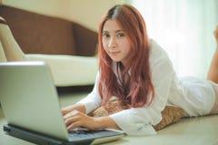 Mujer joven que usa el ordenador portátil Imagenes de archivo
