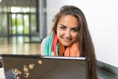 Mujer joven que usa el ordenador portátil Imágenes de archivo libres de regalías