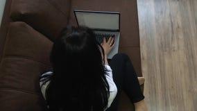 Mujer joven que usa el ordenador portátil en casa que se sienta en el sofá almacen de video