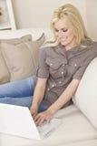 Mujer joven que usa el ordenador portátil en el país en el sofá Imágenes de archivo libres de regalías