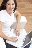 Mujer joven que usa el ordenador portátil en el país en el sofá Imagenes de archivo