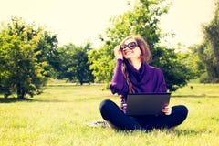 Mujer joven que usa el ordenador portátil en el parque que se sienta en la hierba verde Imagenes de archivo