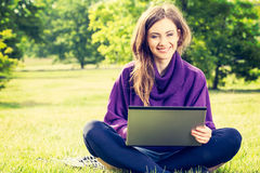 Mujer joven que usa el ordenador portátil en el parque que se sienta en la hierba verde Imágenes de archivo libres de regalías