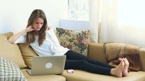 Mujer joven que usa el ordenador portátil en el sofá