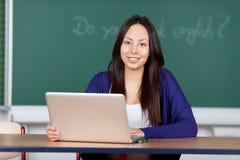 Mujer joven que usa el ordenador portátil en la lección inglesa Fotos de archivo