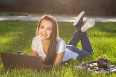 Mujer joven que usa el ordenador portátil en el parque que miente en la hierba verde Concepto de la actividad del tiempo libre Fotos de archivo libres de regalías
