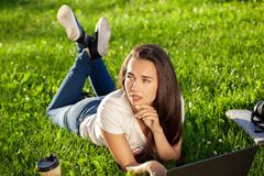 Mujer joven que usa el ordenador portátil en el parque que miente en la hierba verde Concepto de la actividad del tiempo libre Foto de archivo libre de regalías